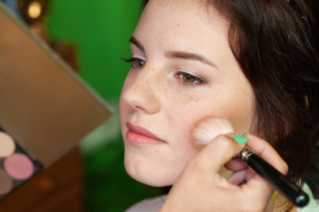 Closeup portrait of a woman, putting on makeup with brush