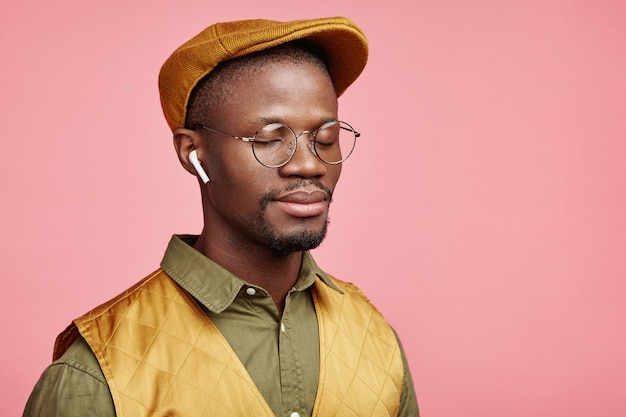 Closeup portrait of young african-american man with hat and wireless headphones