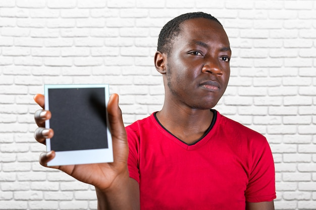 Closeup portrait of young african man holding empty black picture frame with copy space