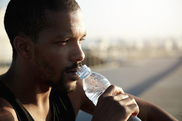 Closeup ritratto di giovane uomo barbuto acqua potabile