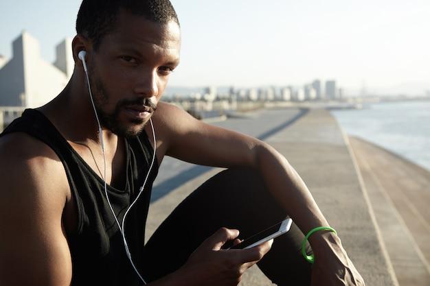 Closeup ritratto di giovane uomo barbuto che ascolta la musica