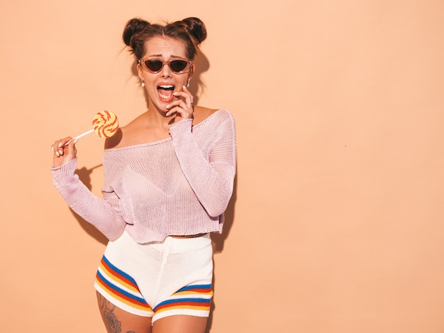 Closeup portrait of young beautiful sexy smiling woman with ghoul hairstyle. trendy girl in casual summer white swimsuit in sunglasses.hot model isolated on beige.eating,biting candy lollipop
