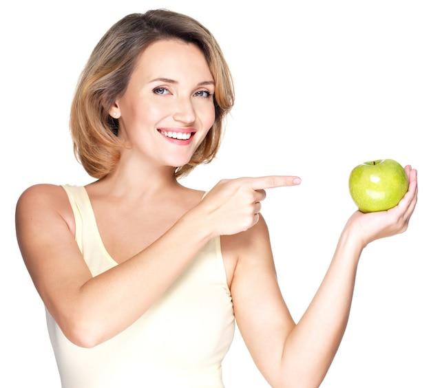 Closeup ritratto di una giovane bella donna sorridente che punta il dito contro la mela isolata su bianco.