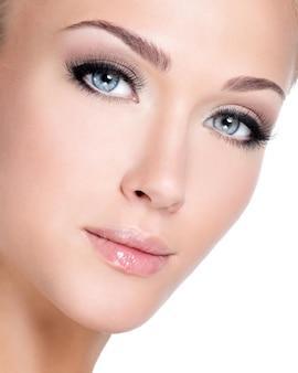 Closeup ritratto di giovane bella donna bianca con lunghe ciglia finte sul muro bianco