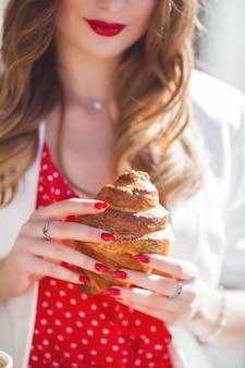 Closeup portrait of young beautiful woman eating croissant.  french girl.
