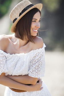 Closeup portrait of young beautiful woman outdoors on the meadow. female in the hat on summertime. lady in white dress.