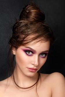 Closeup portrait of young beautiful woman with bright pink smokey eyes modern summer make up