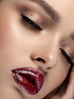 Closeup portrait of young beautiful woman with glittery red lips fashion makeup