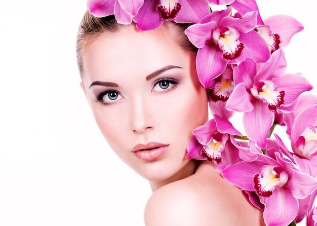 Closeup ritratto di giovane bella donna con una pelle sana e pulita del viso. bella ragazza adulta con fiore vicino al viso. - isolato su muro bianco
