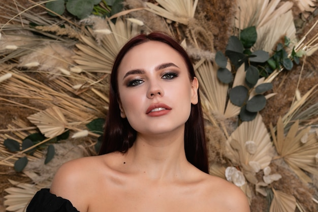 Closeup portrait of young beautiful woman with a healthy skin of the face. brunette girl with burgundy lips on a background of spring dry field flowers. open shoulders