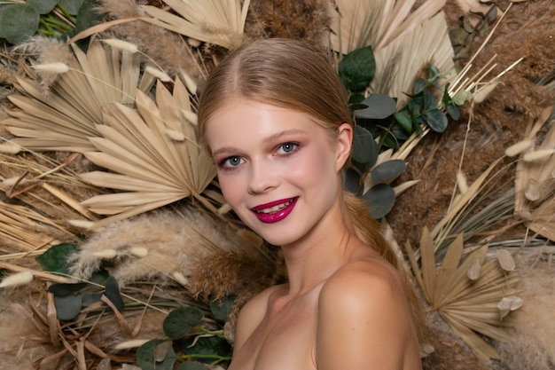 Closeup portrait of young beautiful woman with a healthy skin of the face. looks straight and smiles blonde girl with burgundy lips against a background of spring dry field flowers.