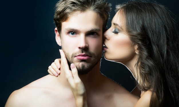 Closeup portrait of young couple kiss sexy woman embracing and kissing muscular man sensual kisses