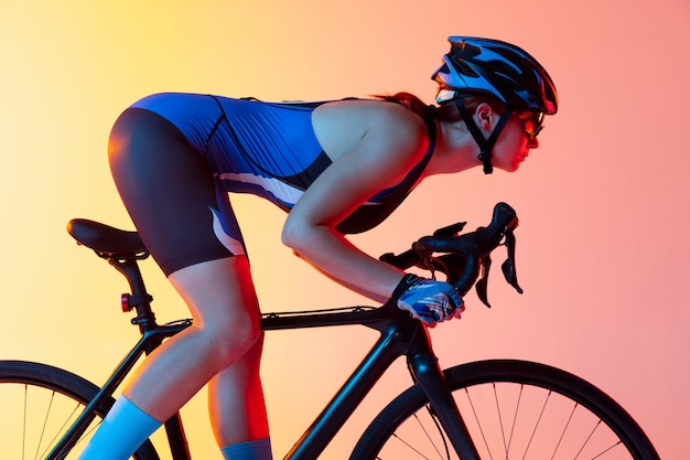 Closeup portrait of young female bike rider on bicycle isolated on gradient wall