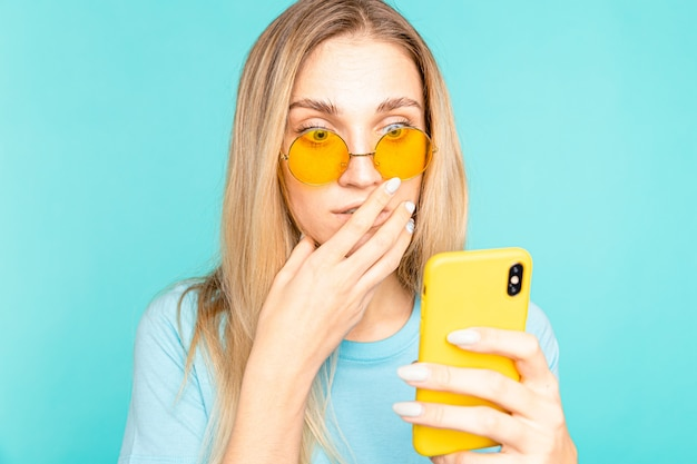 Closeup portrait of young girl looking at phone seeing bad news or photos isolated over blue. human reaction, expression and technology concept.