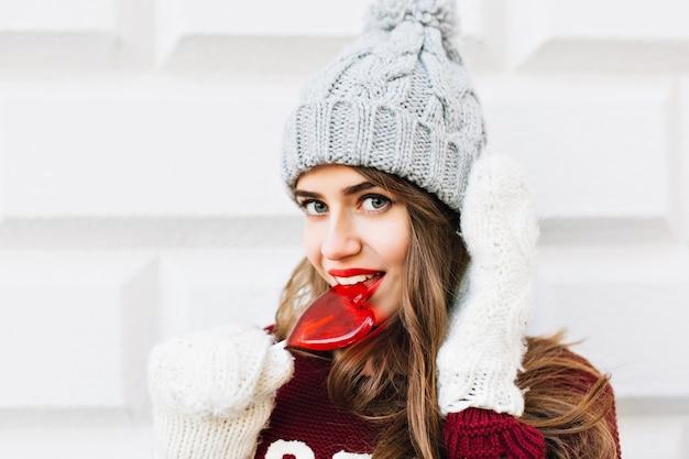 Ragazza del ritratto del primo piano con i capelli lunghi in cappello lavorato a maglia e maglione marsala che lecca lecca-lecca cuore rosso sul muro grigio