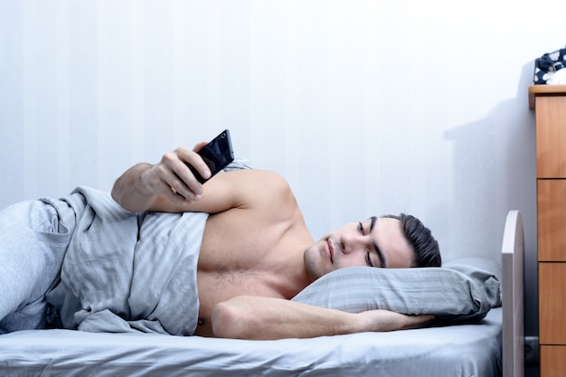 Closeup portrait of a young man, looks at messages on a smartphone in bed at home in the morning