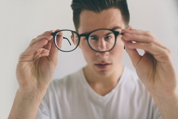 Closeup portrait of young man with glasses. he has eyesight problems and is squinting his eyes a little bit. handsome guy is holding his eyeglasses right with one hand. the concept