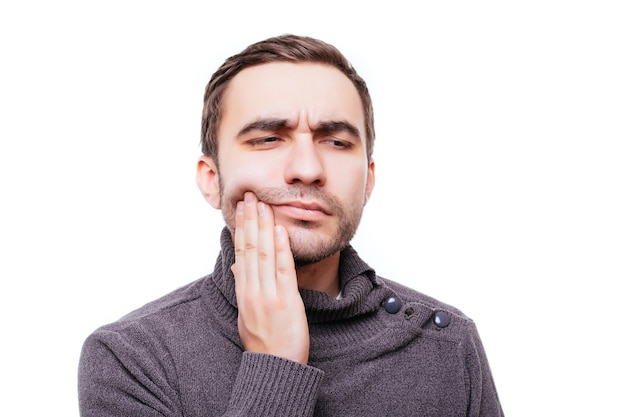 Closeup portrait of young man with tooth ache crown problem about to cry from pain touching outside mouth with hand, isolated on white wall
