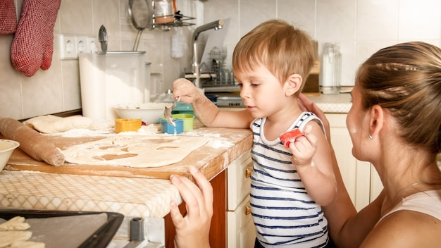 Closeup portrait of young mother with toddler boy holding baking pan and making cookies on kitchen