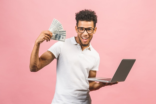 Closeup portrait, young successful african american business man making money from internet, holding cash in hand, laptop in another,