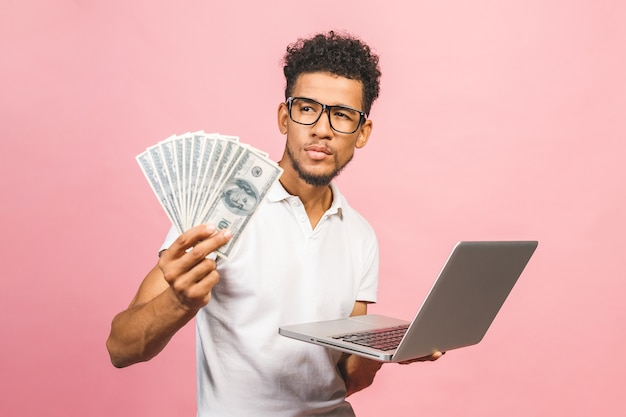 Closeup portrait, young successful african american business man making money from internet, holding cash in hand, laptop in another