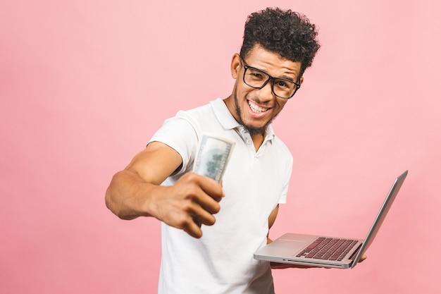 クローズアップの肖像画、インターネットからお金を稼ぐ若い成功したアフリカ系アメリカ人のビジネスマン、手に現金を持って、別のラップトップ