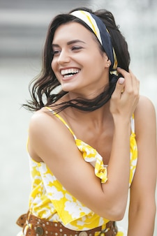Closeup portrait of young very beautiful woman outdoors. lady in the yellow dress on summertime. women`s accessories. female with kerchief.