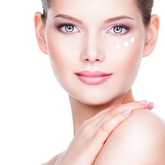 Closeup ritratto di giovane donna che applica la crema sul suo bel viso - su un muro bianco.