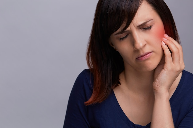 Closeup portrait of young woman on grey background suffering from toothache