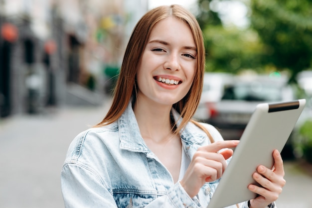 Closeup portrait of young woman holding an ipad and standing outdoor