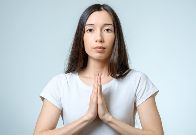 Closeup portrait of a young woman praying isolated