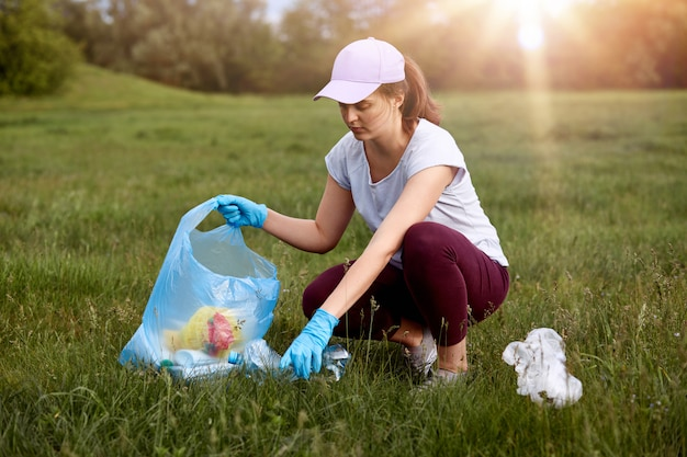 Closeup portrait of young woman wearing t shirt, trousers and baseball cap, picking up rubbish in meadow to garbage bag, posing in field during sunset.
