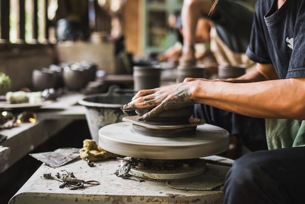 Closeup potter's hands shaping soft clay to make an earthen pot
