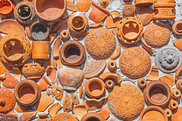 Closeup pottery thai and brown texture background on wall for interior or exterior decoration.