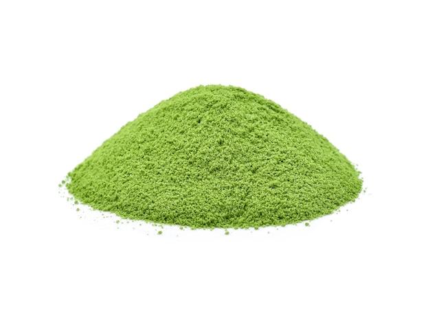 Крупный план порошкообразный зеленый чай, изолированные на белом.