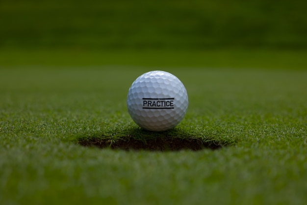 Closeup of a practice text written on a golf ball on the lawn under the sunlight