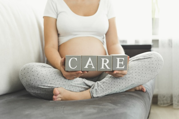 단어 케어를 만드는 편지를 들고 근접 촬영 임신 한 여자