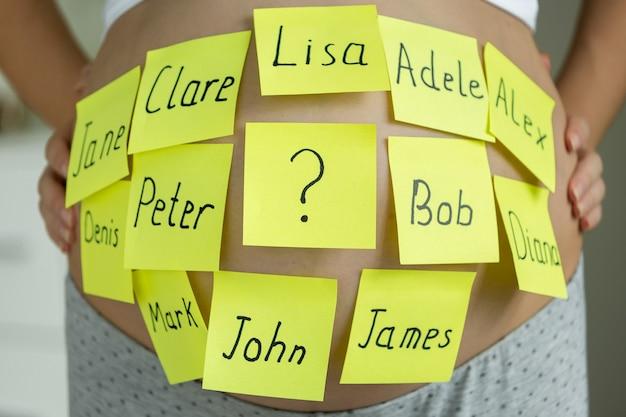 Крупным планом беременная женщина с именами детей на памятных наклейках на животе