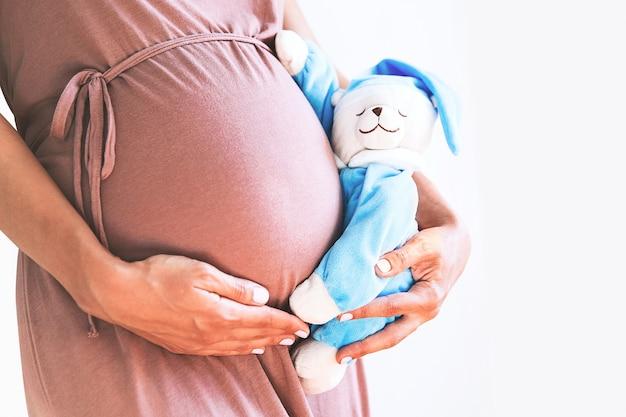 テディベア妊娠コンセプトとクローズアップ妊娠中の女性の腹