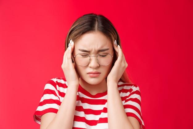 근접 촬영 압력 고민 젊은 아시아 여자 잡아 머리 터치 사원 인상을 찌푸리고 가까이 눈을 구부리...
