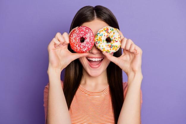 Красивая дама крупным планом держит свежие глазированные пончики, похожие на спецификации
