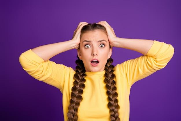 머리에 팔을 들고 근접 촬영 예쁜 아가씨 긴 머리띠는 착용 캐주얼 노란색 점퍼 절연 보라색 컬러 벽입니다