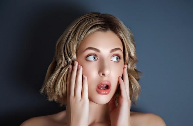 젊은 여자의 근접 촬영 예쁜 초상화는 그녀의 얼굴에 그녀의 손으로 무서 워. 여성 배우 감정 흉터