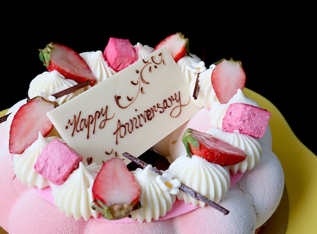 Closeup of a pretty strawberry mousse cake with an edible white chocolate greeting card on top