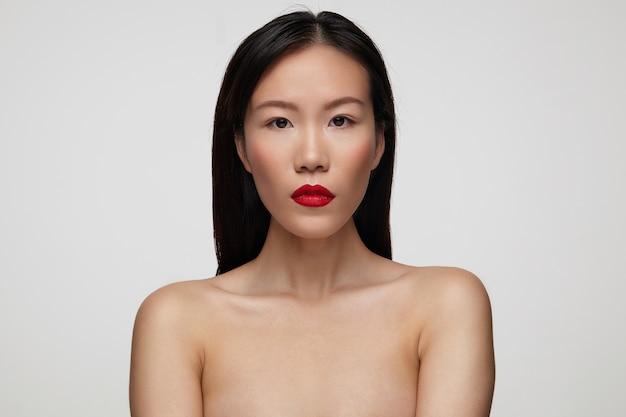 Primo piano di bella giovane donna castana con trucco festivo mantenendo le sue labbra rosse piegate mentre guarda seriamente, isolato sopra il muro bianco