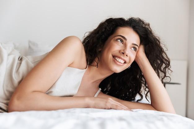 ホテルのベッドに横たわっているシルクのレジャー服を着て、手で頭を支えながら脇を見て長い巻き毛のクローズアップかなり若い女性20代
