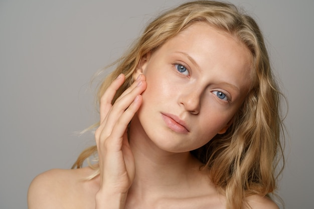 Closeup of pretty young woman face with blue eyes, curly natural blonde hair, has no makeup, touching her soft skin, standing shirtless with bare shoulders, looking at camera. studio grey background