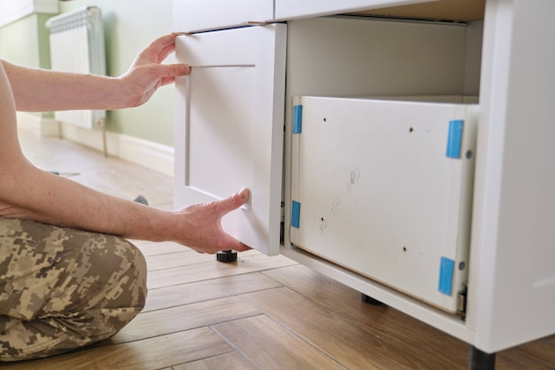 Closeup process of assembling kitchen furniture, hands of male worker