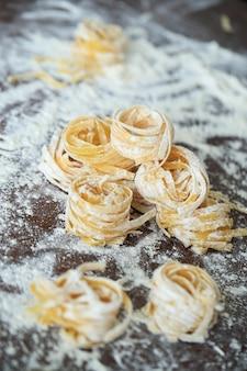 Closeup of process of making cooking homemade pasta.
