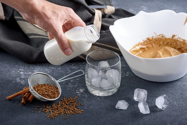 Closeup process of making dalgona coffee, korean drink on gray kitchen table, hand pours milk into ice glass